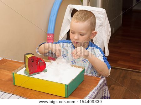 boy in striped shirt sitting at the table and doing crafts