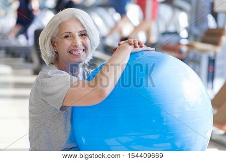 Finishing training. Pleasant beautiful senior woman smiling and keeping fit ball while sitting on a floor in a gym.