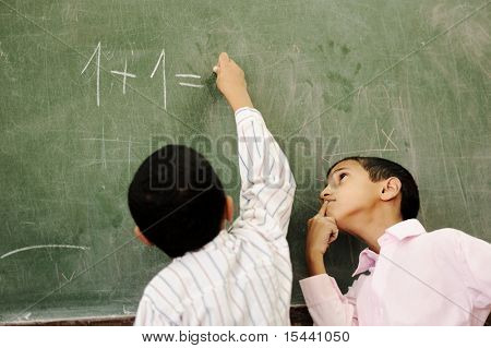 Two boys in classroom thinking, writing and counting on board