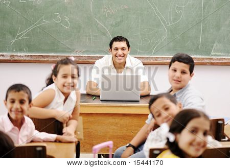 Happy young teacher and children in classroom together
