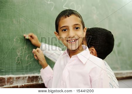 Boys drawing and writing on board in school