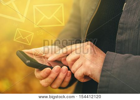 Sending SMS messages on mobile phone in autumn computer generated envelopes for outgoing communication