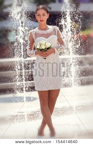 Young slim bride in front of a fountain with crossed legs