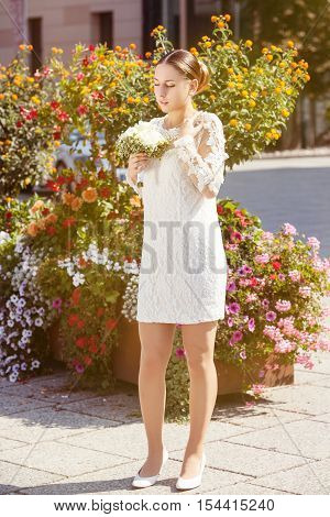 Gorgeous young bride outdoors in her wedding dress