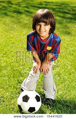 Lindo niño jugando con una pelota en el Parque de la naturaleza