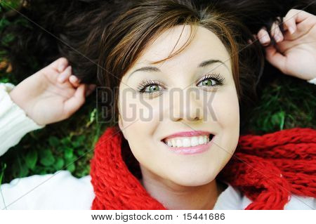 Young beauty girl laying on autumn ground and leaves, perfect face and natural white healthy smiling teeth, fashionable fall clothes