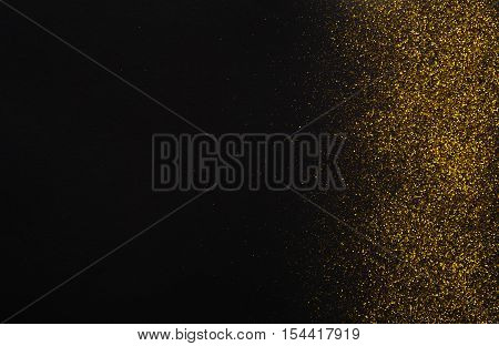Golden glitter sand texture border on black, abstract background with copy space. Yellow dusty shimmer decoration, shiny and sparkling. Holidays and glamour concept.