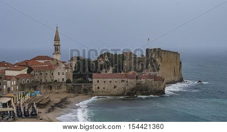BUDVA, MONTENEGRO - OCTOBER 21 2016: Heavy rain over Budva hid the mountains in background and provided a unique and clear view over the old town with Sv. Ivan church and city citadel with fortified walls