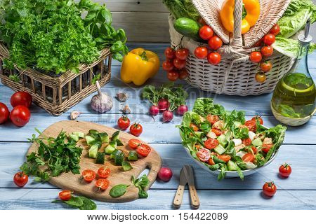 Preparing a healthy vegetable salad on old wooden table