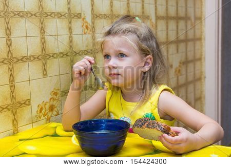 Little girl eating soup reluctantly the table in the kitchen