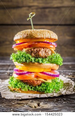 Double-decker homemade burger made from fresh vegetables on wooden table