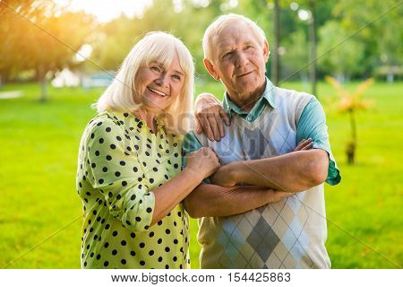 Senior couple on park background. Man and smiling woman. Being together and staying strong. We live a happy life.