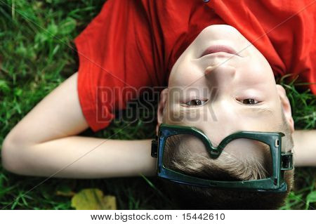 Cute positive boy, a little pilot,  with glasses laying on green grass ground and looking up at camera and thinking, dreaming about the future