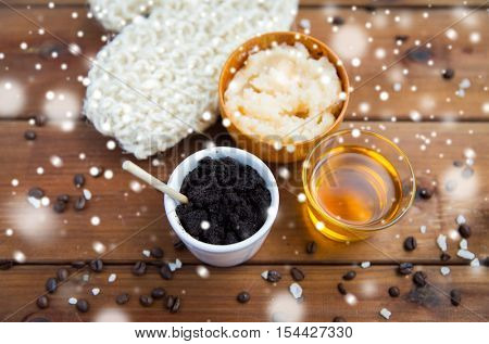 beauty, spa, bodycare, bath and natural cosmetics concept - coffee scrub in cup with honey and wisp on wooden table over snow