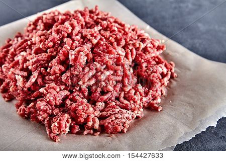 Pinky raw ground beef on a craft paper. Ground beef can be used to cook hamburgers, chili con carne or other dishes. Stone cement background