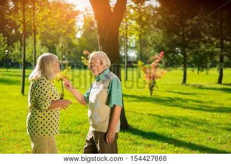 Man points finger at lady. People on background of park. You're testing my patience. Tired of quarrels.