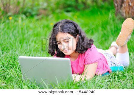 crianças felizes na natureza ao ar livre, pequena menina trabalhando e jogando no laptop, imposição Prado Verde