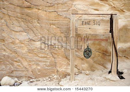 The Siq in Petra, Jordan - copy-space wooden banner with an arrow on. You also can simply remove the text and put your own.