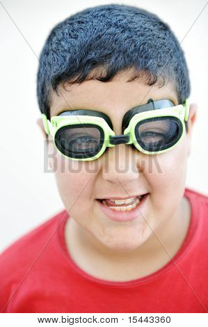 Happy funny cute  boy with the pool swimming goggles, closeup portrait