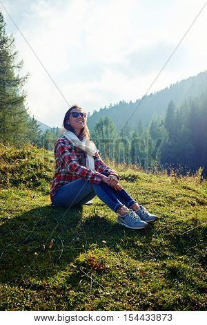 woman is looking at the sky, enjoying the picturesque vista of the mountains. Wearing checked shirt and jeans with a scarf on the neck