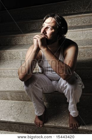 Thoughtful man on black background in low key, sitting on stairs