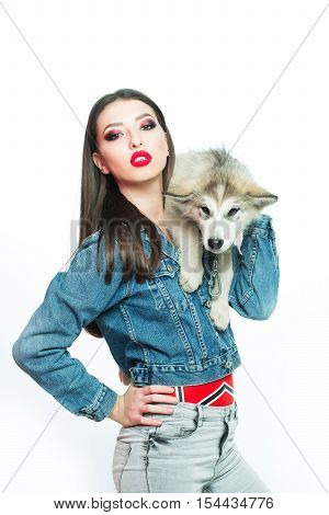 pretty sexy brunette woman with long straight hair fashion makeup in denim look holding cute little dog of husky isolated on white background