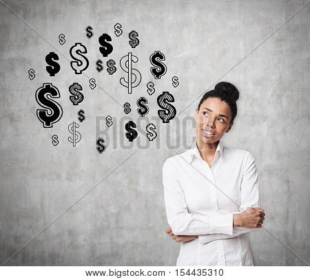 African American girl is standing against concrete wall with dollar signs on it and thinking. Concept of earning money