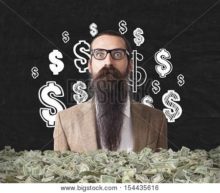 Baffled man with long beard is buried in packs of dollars and standing against black wall with dollar signs. Concept of being rich