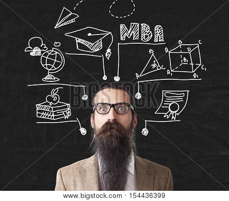 Baffled man with long beard is standing near blackboard with education icons. Concept of nuts professor