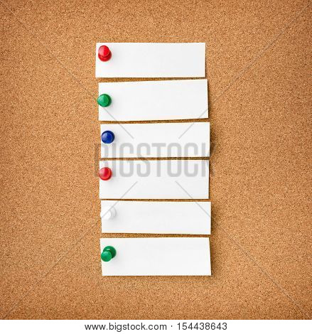 Close up front view of illustrative corkboard with blank white note cards pinned with colorful pins on pinboard background.