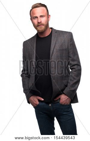 Wealthy confident relaxed young man in black shirt, denim jeans and blazer looking at camera with hands in pockets. Full body length portrait isolated over white studio background