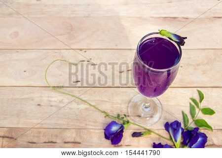 Butterfly pea juice in glass on wooden table with flower.