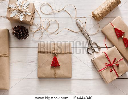 Creative hobby. Wrapping christmas holiday handmade present in craft paper with twine ribbon. Scissors and gift boxes with bows and snowflakes on white wooden table, top view.