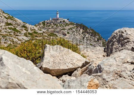 Lighthouse on the beach. View of the lighthouse and sea from the rocky mountain of Spain.