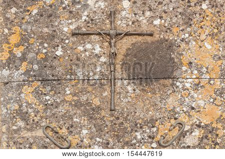 Metal cross. Close up photo of crucifix of Jesus Christ on the stoned plate.