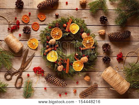 Christmas wreath with natural decorations, pine cones spruce, nuts, candied fruit on a rustic wooden table. Christmas decorations.