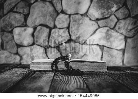 prayer beads with a cross on an open old book on old wooden table on a background of stone walls. selective focus black & white photo. with space for your text
