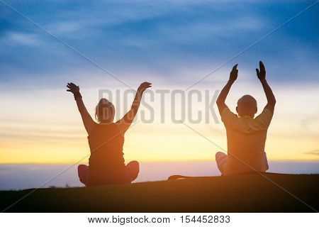 Couple doing yoga. People on sunset sky background. Strive to harmony. Way to peace and balance.