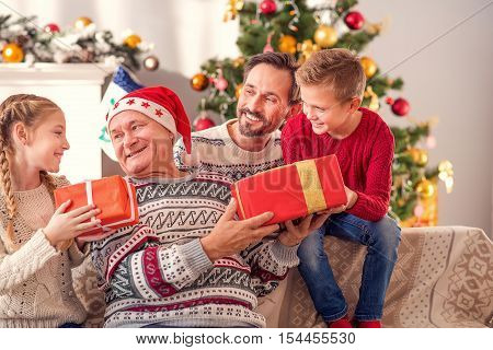 Merry Christmas. Friendly family is giving presents to old man. Grandfather is sitting on sofa and smiling happily