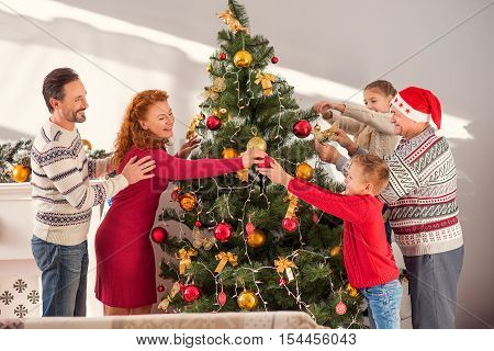 Joyful married couple is celebrating Christmas with their children and grandfather. They are decorating fir-tree and laughing