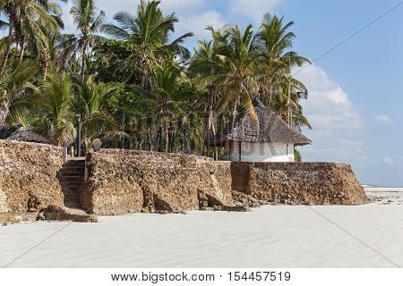 Indian Ocean coastline. The sandy Indian Ocean coastline with a paved embankment small pretty gazebo and large palms.