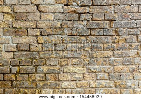 Brick wall. Brick wall. Brick wall with bricks of different sizes and shapes of gray color with addition of sand color.