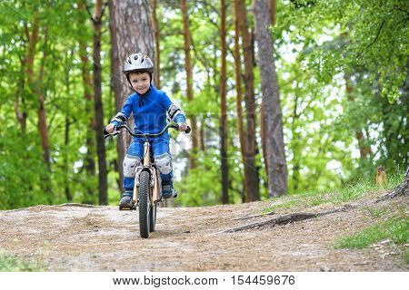 Happy Funny Little Kid Boy In Colorful Raincoat Riding His First Bike On Cold Day In Forest. Active