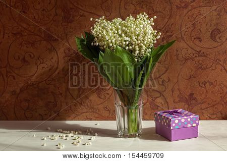 Vase with lilies of the valley. Vase with lilies of the valley on a background of brown wall with floral pattern. And the modest little present nearby.
