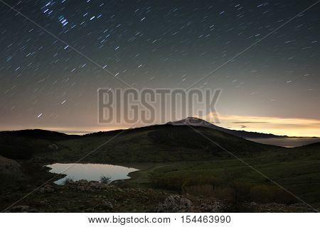 Lake Nebrodi Park and volcano Etna beneath stars trails, Sicily