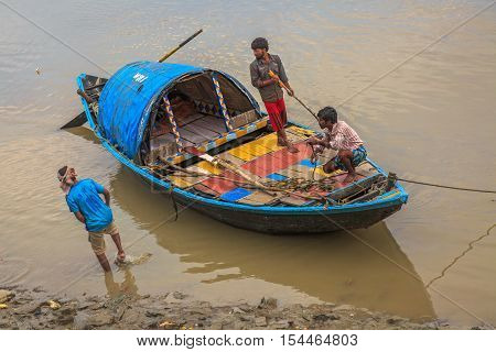 KOLKATA, INDIA - OCTOBER 31, 2016: Wooden country boat stuck in mud at low tide on the Ganges river near Outram ghat, Kolkata. Fishermen trying to get the boat offshore.