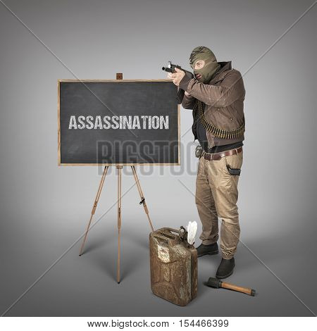Assassination text on blackboard with terrorist holding machine gun