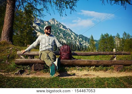 Mid low angle shot of handsome bearded man who is having a break during the mountainous walk. Admiring the vista of mountains, feeling peace and calm