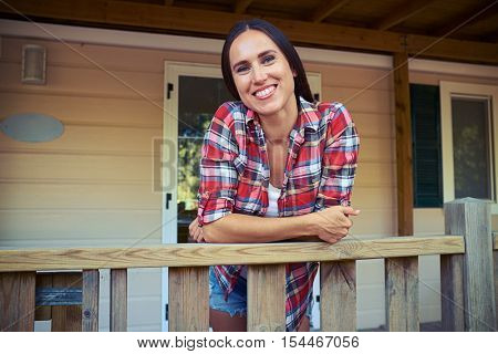 Close-up of charming woman who is standing on the porch of a rest house. Looking happy and relaxed while having a rest during the summer vacation
