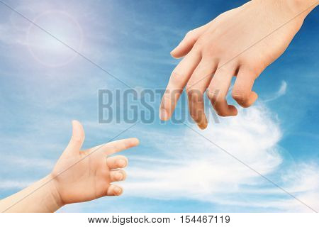 Father and child hands reaching to each other on sky background. Help and care concept.